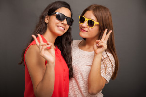 Portrait a couple of teenage girlfriends wearing sunglasses and doing a peace sign with their hands